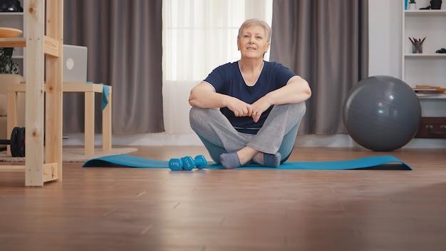 Portret van senior vrouw zittend op yoga mat. actieve gezonde levensstijl sportieve oude persoon training workout thuis wellness en indoor training