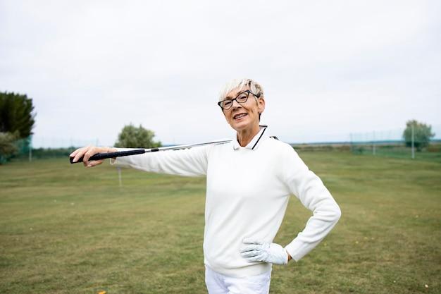 Portret van senior vrouwelijke golfer met golfclub staande op de golfbaan.