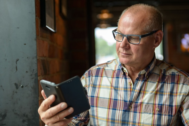 Portret van senior zakenman met behulp van telefoon in de koffieshop