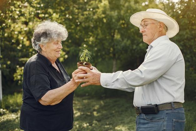 Portret van senioren in een hoed tuinieren