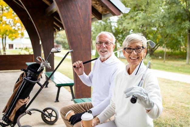 Portret van senioren met pensioen die golfclubs vasthouden en klaar zijn voor golftraining.
