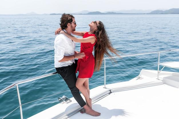 Portret van sensueel kaukasisch paar geknuffel op luxe wit jacht op zee. knappe man hugs zijn vrouw in een rode jurk