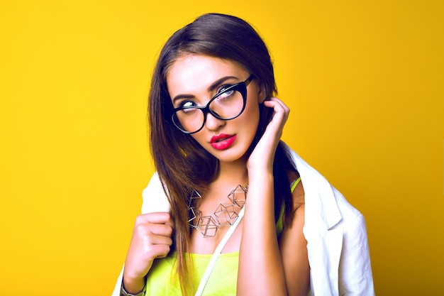 Portret van sensuele jonge vrouw, lange donkerbruine haren, retro bril, zakelijke lichte casual look
