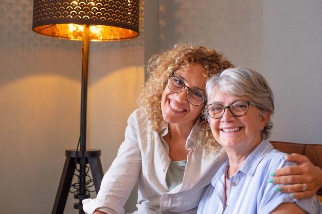 Portret van serene en lachende senior moeder en volwassen blonde dochter, knuffelen zittend op de bank thuis