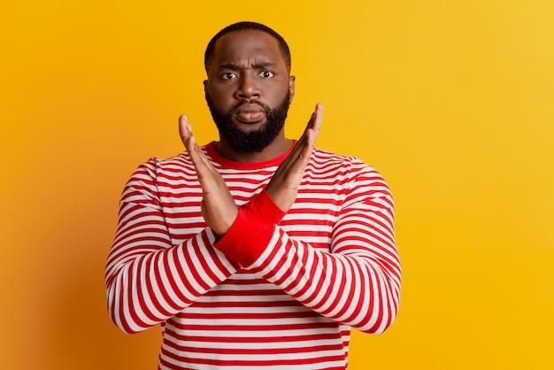 Portret van serieuze coole man maakt protestgebaar kruis handen op gele muur