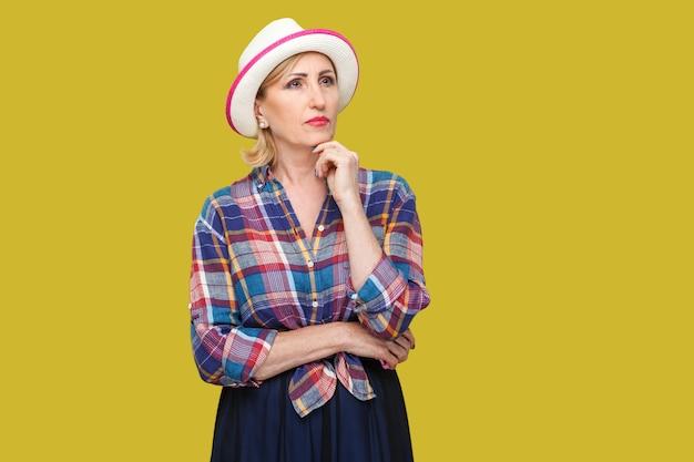 Portret van serieuze doordachte moderne stijlvolle volwassen vrouw in casual stijl met witte hoed die staat, haar kin aanraakt, vraagt en denkt wat te doen. indoor studio opname geïsoleerd op gele achtergrond.