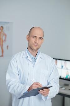 Portret van serieuze huisarts in witte laboratoriumjas die patiëntengegevens in document schrijft