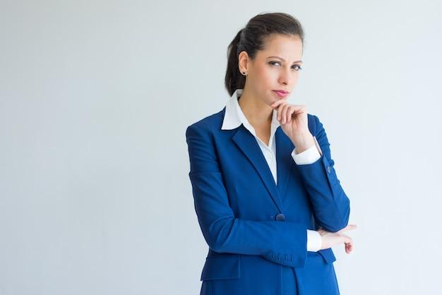 Portret van serieuze jonge vrouw in blauwe formele pak.