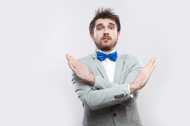 Portret van serieuze knappe bebaarde man in casual grijs pak en blauwe vlinderdas staande met gekruiste armen, x teken handen en kijkend naar de camera. indoor studio opname, geïsoleerd op lichtgrijze achtergrond.