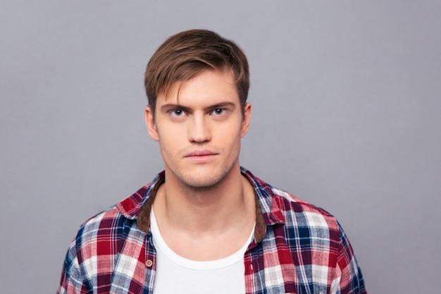 Portret van serieuze knappe jongeman in geruit hemd over grijze muur