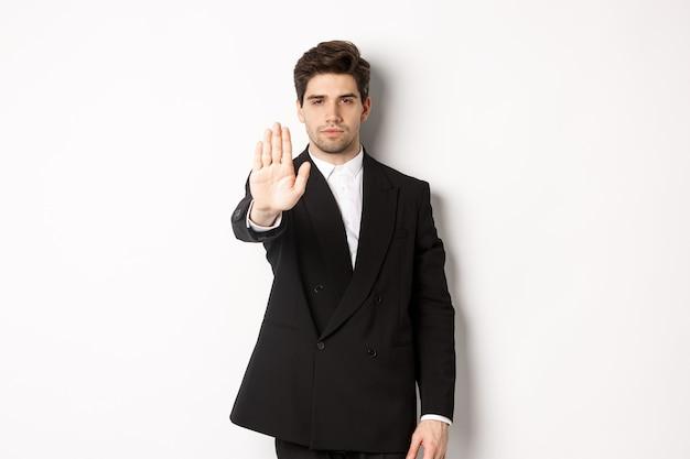 Portret van serieuze knappe man in formeel pak, hand uitstrekkend om je te stoppen, actie te verbieden, te verbieden en ergens mee oneens te zijn, staande tegen een witte achtergrond
