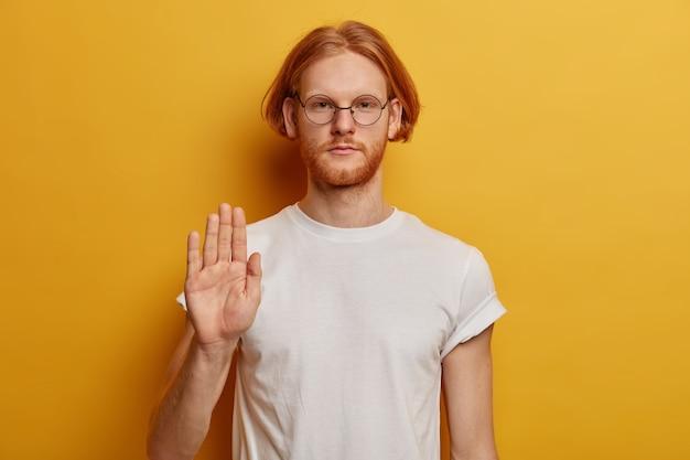 Portret van serieuze man student werpt palm in stopgebaar, weigert iets te doen