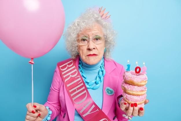 Portret van serieuze, mooie, volwassen dame kijkt, met melancholische uitdrukking houdt stapel geglazuurde heerlijke donuts vast met opgeblazen ballon geglazuurde donuts viert 102e verjaardag
