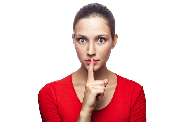 Portret van serieuze vrouw in rode t-shirt met sproeten met shh-teken op haar lippen