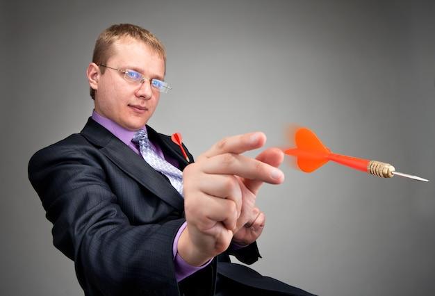 Portret van serieuze zakenman die rode pijl gooit