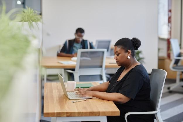 Portret van serieuze zakenvrouw die op laptop werkt en e-mails van collega's en klanten beantwoordt