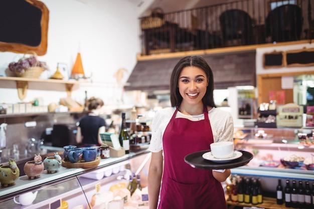Portret van serveerster die een kop van koffie dient