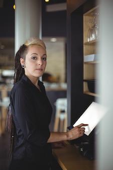 Portret van serveerster die kasregister gebruiken bij teller