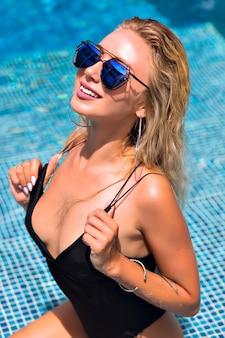 Portret van sexy blonde vrouw bij het zwembad