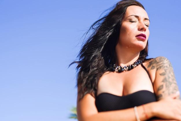 Portret van sexy brunette met gesloten ogen die op het strand stellen