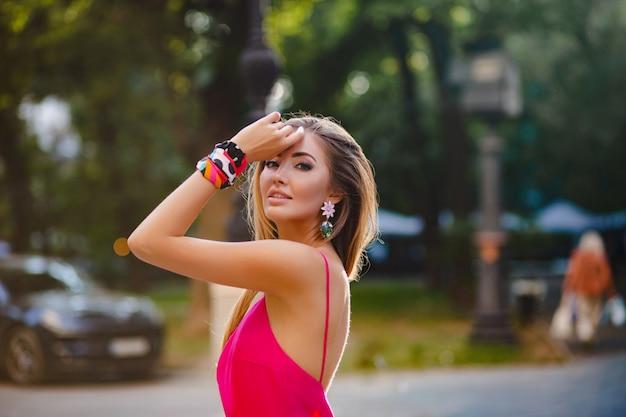 Portret van sexy elegante aantrekkelijke vrouw in roze sexy zomerjurk wandelen in straat