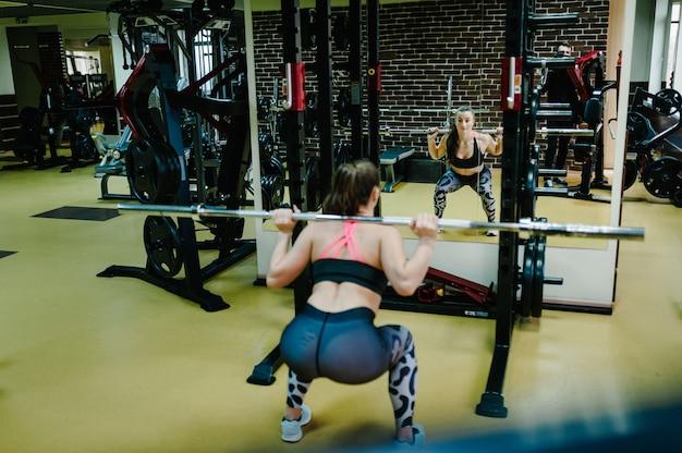Portret van sexy gespierde vrouw die sportkleding draagt die gewichtheffen oefening doet