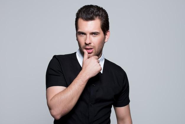 Portret van sexy jonge man in zwart shirt met hand in de buurt van gezicht vormt over grijze muur.