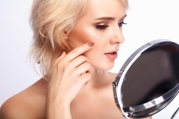 Portret van sexy jonge vrouw die met verse gezonde huid binnen in spiegel kijken.