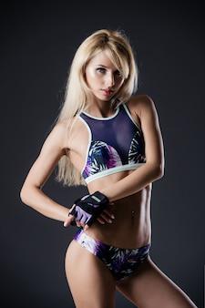 Portret van sexy jonge vrouw met haar handen op de heupen camera kijken. geschiktheidswijfje met spierlichaam klaar dragend handhandschoenen voor training op grijs
