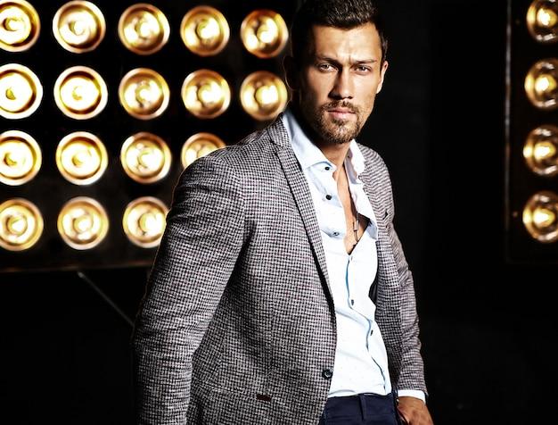 Portret van sexy knappe mode mannelijk model man gekleed in elegant pak op studio lichten achtergrond