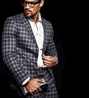 Portret van sexy knappe mode mannelijk model man gekleed in elegant pak op zwarte achtergrond