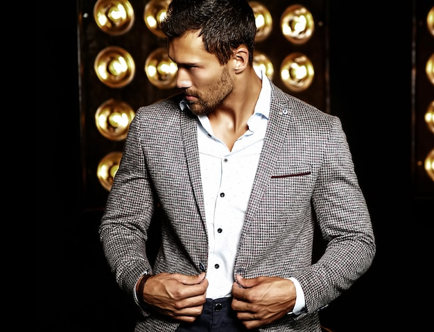 Portret van sexy knappe mode mannelijk model man gekleed in elegant pak op zwarte studio lichten achtergrond