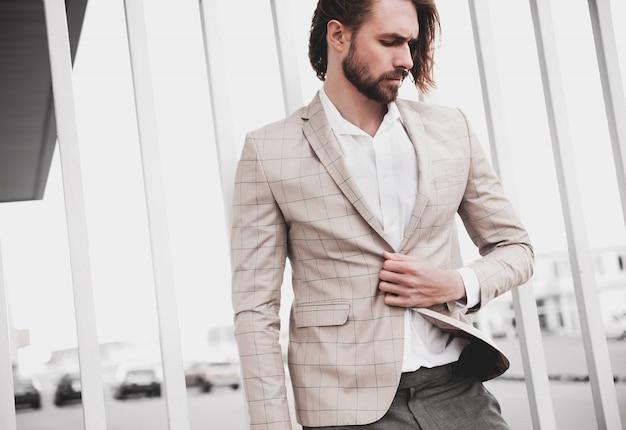 Portret van sexy knappe mode mannelijk model man gekleed in elegante beige geruit pak die zich voordeed op de straat achtergrond