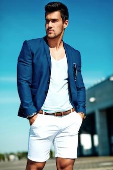 Portret van sexy knappe mode mannelijk model man gekleed in elegante pak die zich voordeed op de straat achtergrond. blauwe lucht