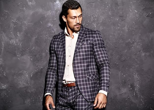 Portret van sexy knappe mode mannelijk model man gekleed in elegante pak poseren in de buurt van grijze muur