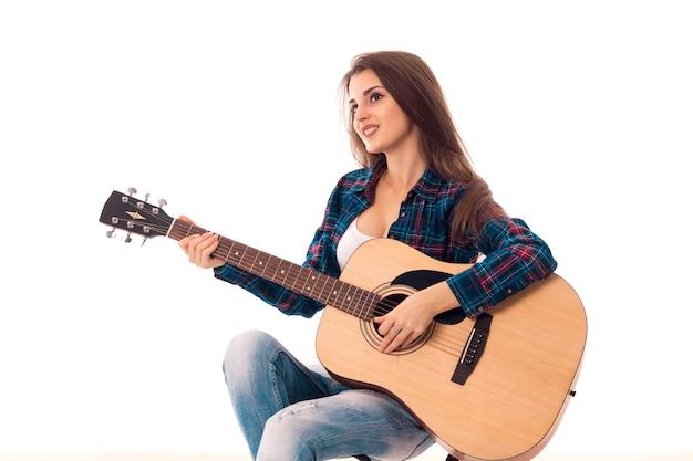 Portret van sexy meisje met gitaar in handen glimlachend geïsoleerd op witte achtergrond