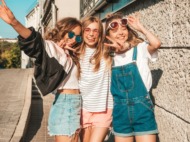 Portret van sexy onbezorgde vrouwen die dichtbij muur in de straat stellen positieve modellen die pret in zonnebril hebben