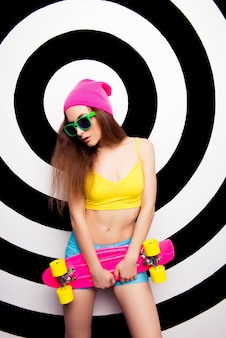 Portret van sexy slanke vrouw in hoed en bril met skate