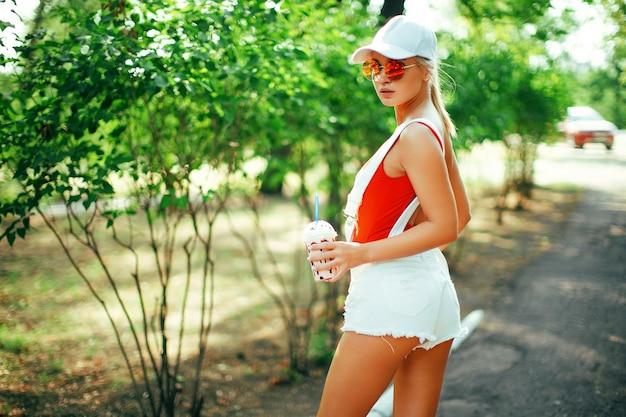Portret van sexy stijlvolle mode meisje met afgeronde zonnebril rode zwembroek witte baseball cap sho...