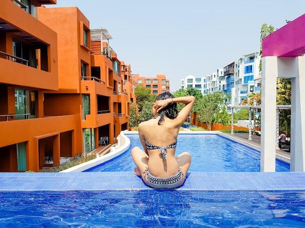 Portret van sexy vrolijke vrouw ontspannen bij het luxe zwembad