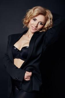 Portret van sexy zakelijke vrouwen blond in een zwart jasje, blote lichaam, perfecte figuur meisjes, erotische sensuele look, gedurfd beeld, de vrouw in het zwart