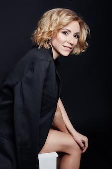 Portret van sexy zakelijke vrouwen blond in een zwart jasje, blote lichaam, perfecte figuur meisjes, sensuele look, gedurfd beeld, de vrouw in het zwart