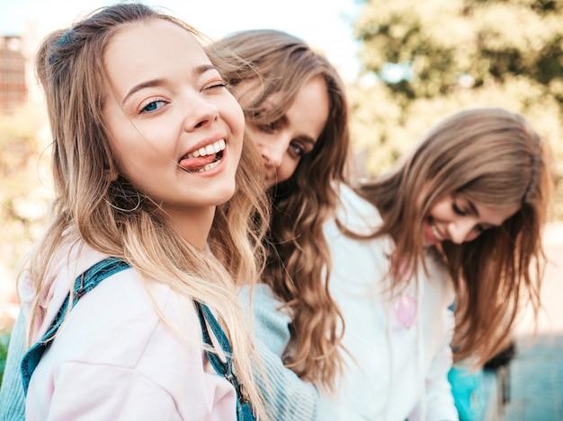 Portret van sexy zorgeloze vrouwen die zich voordeed op de straat achtergrond. positieve modellen plezier. knipperen en toont tong