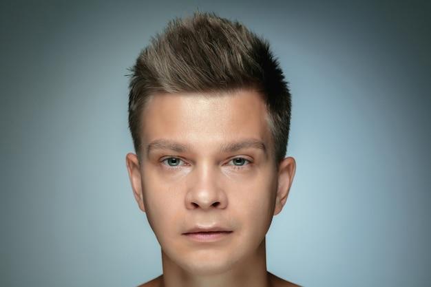 Portret van shirtless jonge man geïsoleerd op een grijze muur. kaukasisch gezond mannelijk model camera kijken en poseren. concept van de gezondheid en schoonheid van mannen, zelfzorg, lichaams- en huidverzorging.