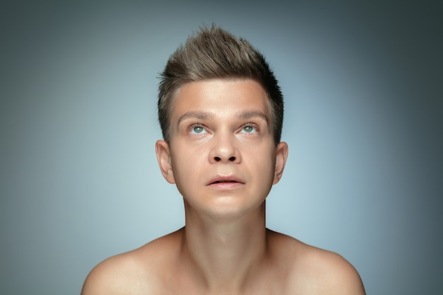 Portret van shirtless jonge man geïsoleerd op een grijze muur. kaukasisch gezond mannelijk model opzoeken en poseren. concept van de gezondheid en schoonheid van mannen, zelfzorg, lichaams- en huidverzorging.