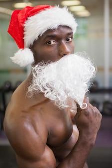 Portret van shirtless macho man in kerstmuts