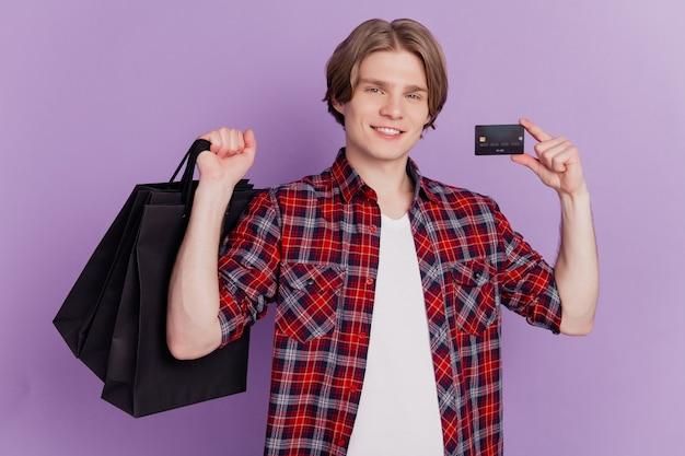 Portret van shopaholic man houdt winkelkoopjes creditcard brede glimlach op paarse achtergrond