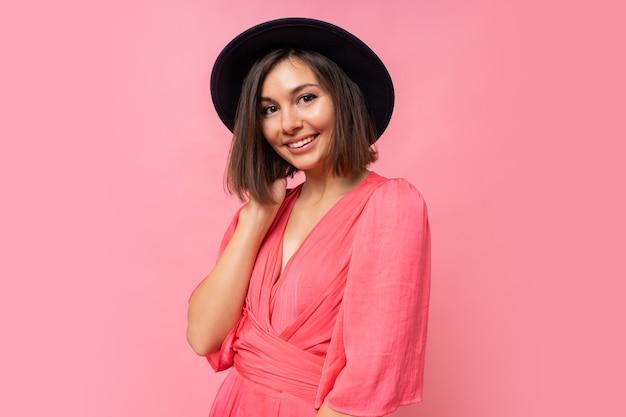 Portret van sierlijke brunette vrouw in roze jurk