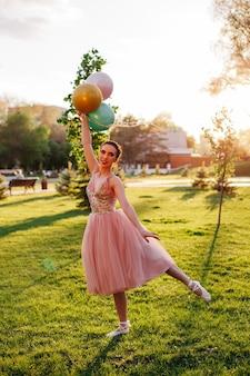 Portret van slanke ballerina in een roze zijden jurk en witte spitzen die staan en balanceren op ...