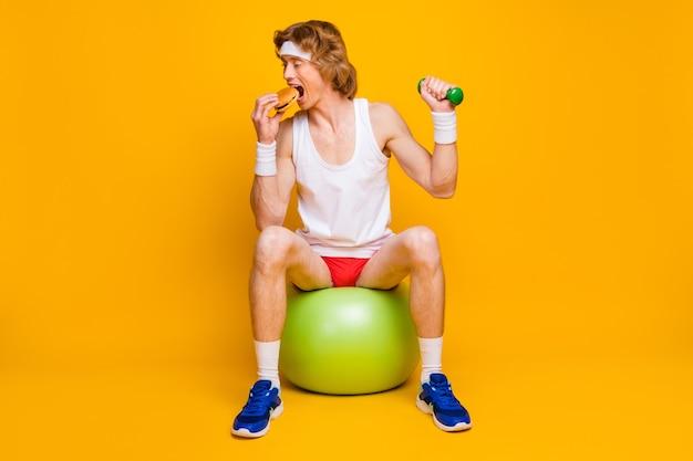 Portret van slanke dunne man zittend op fitball lekker fastfood eten trainen